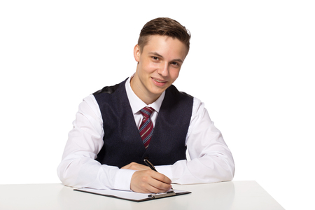 Smiling young businessman working in office, sitting at desk, writing notes to clipboard. Stock Photo