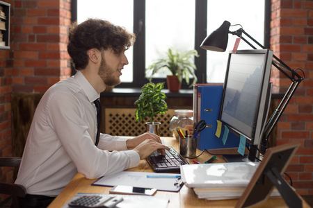 Young smiling business man working on computer