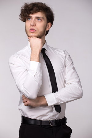 Portrait of handsome serious pensive man in white shirt, looking upwards thinking about problem, holding his chin.