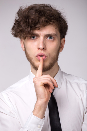 Serious young beard man keeps finger on lips, want to be conspiracy or make silence Stock Photo