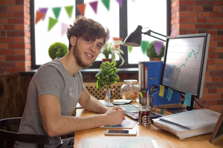 Young smiling man working at his workplace