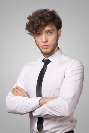 Confident young man in shirt and with arms folding and looking at camera