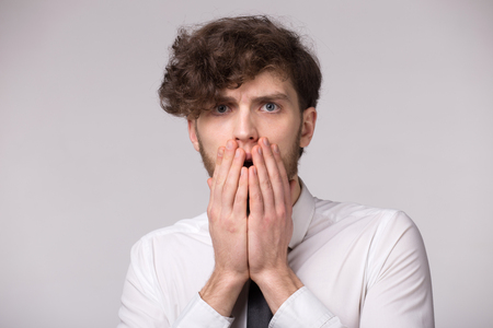 Portrait of young man with shocked emotional facial expression