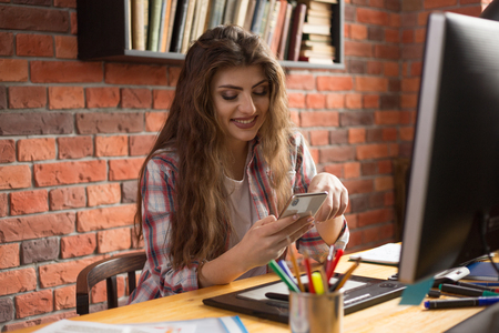 Young Beautiful female desiner or graphic artist at work place typing a message on a telephone.