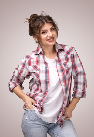 Portrait of a young smiling woman in plaid shirt and white t-shirt, standing with arms in pockets