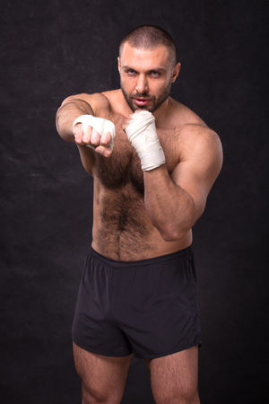 Young muscular boxing fighter training kicks. Kickboxer making a fighting exercise.