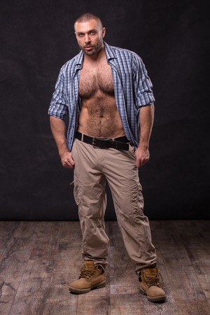 Brutal muscular man, in jeans and cotton shirt. Bodybuilder relaxing standing. Stock Photo