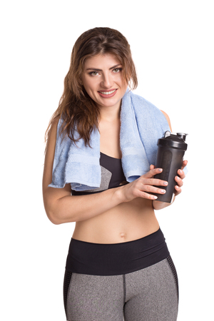 Young athletic smiling woman with a shaker and a towel.
