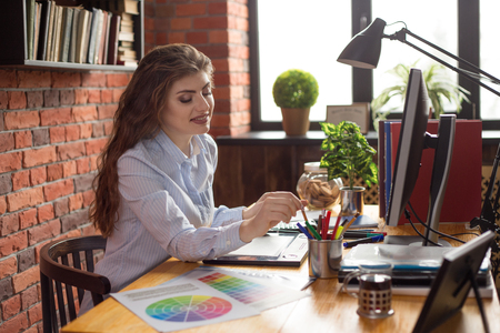 Young Beautiful female desiner or graphic artist at work place at loft style office.