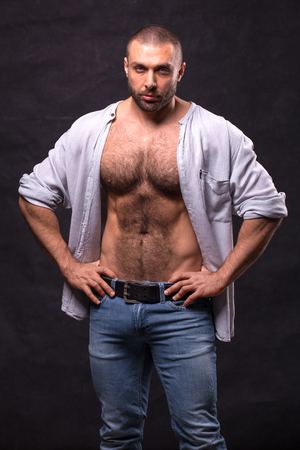 Brutal muscular man, in jeans and cotton shirt. Bodybuilder relaxing standing over dark background.