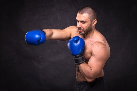 Young muscular kickboxing fighter practicing kicks. Kick boxer doing an exercise for the fight. Concept of a healthy lifestyle. Dark black background.