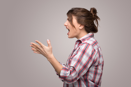 Profile of an angry rage young woman shouting isolated on a gray