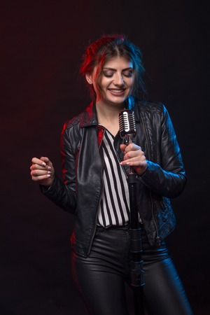 Portrait of expressive rock singer wearing leather jacket and keeping retro style microphone.