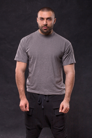 Handsome muscular beard man standing in studio over dark background