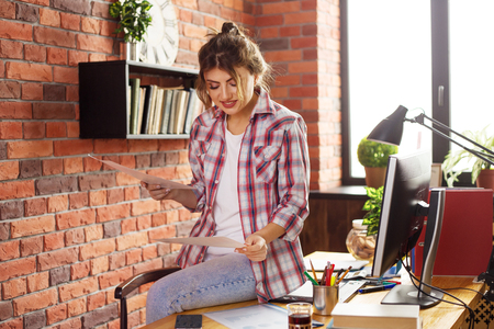 Young female with long hair working at home or in a loft style office. She holding a paper and smiling. Cup of coffee or tea on the desk
