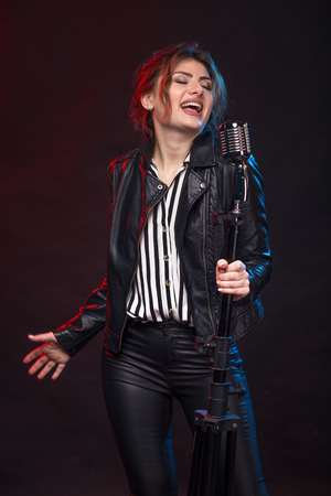 Portrait of expressive rock singer wearing leather jacket and keeping retro style microphone. On smoky dark scene. Stock Photo