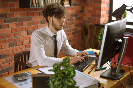 Young smiling business man working on computer in loft style office