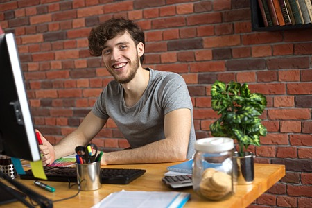 Young smiling man writing with a marker at his workplace in loft style office Stock Photo
