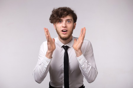 Portrait of young man with shocked emotional facial expression and hands gesture on light gray background Stock Photo