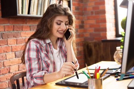 Young female with long hair working with graphic tablet at home or in a loft style office. She talking on a phone and smiling. Stock Photo