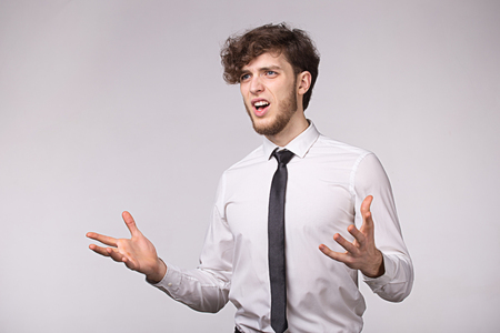 Angry furious businessman shouting out loud with hands up over gray background