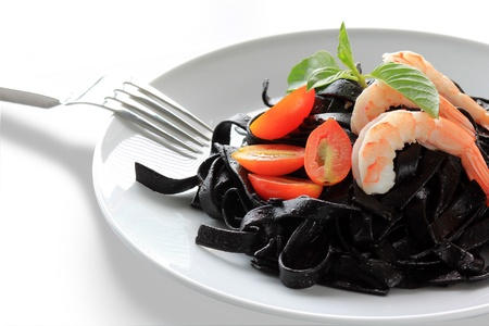 Black tagliatelle (pasta made with cuttlefish ink) with raw tomato Stock Photo