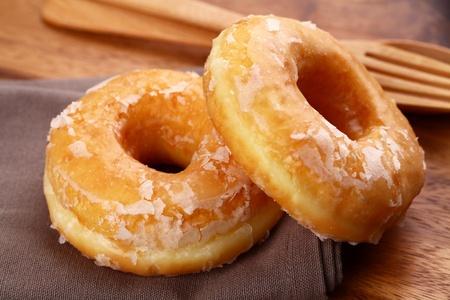 A sugar glazed donut on wood