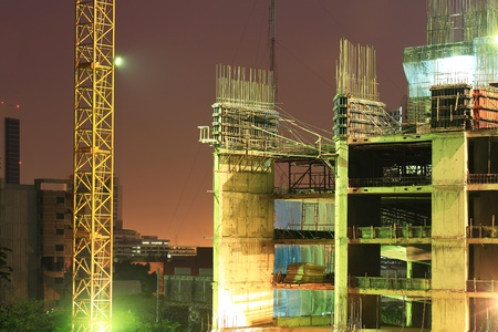 High rise concrete building construction with a yellow crane Editorial
