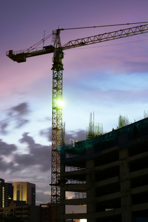 High rise concrete building construction with a yellow crane  photo