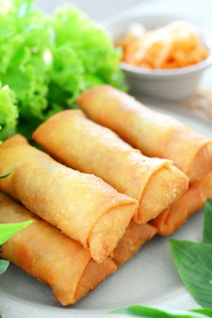 vietnamese food: crispy spring rolls on dish with vegetable