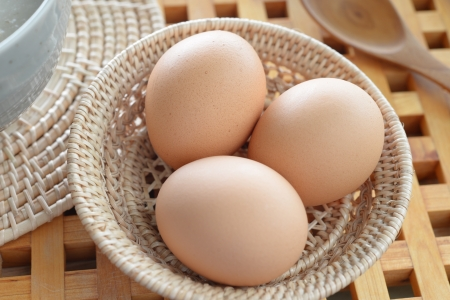 three Brown eggs in a Wicker basket  Stock Photo