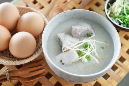 Fish Porridge (congee) served on wood table with eggs Standard-Bild