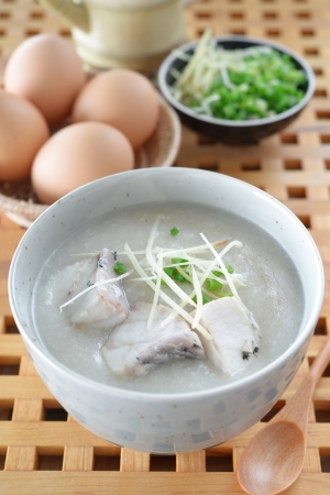 Fish Porridge (congee) served on wood table with eggs Banco de Imagens