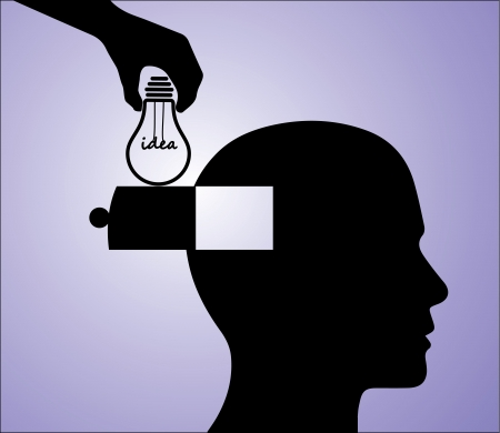 A hand inserting an light bulb idea into a man s head photo