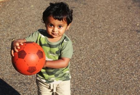 ni�os jugando parque: Un ni�o indio joven que juega con una bola roja en una hierba verde de un jard�n o un parque Foto de archivo