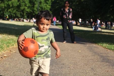 Een jonge Aziatische of Indiase peuter die met een rode bal in de hand op een weg naast een groene gras van een tuin of een park