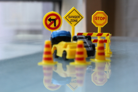 cordoned: car Accident zone cordoned off with a yellow stop sign post. two cars with a major collision with one car toppled by another brown car & area cordoned by yellow barricades Stock Photo