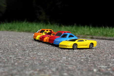 miniature colorful cars standing in line on road sale concept. Different colored cars - blue, yellow, orange, white and red color cars standing side by side on road next to grass photo