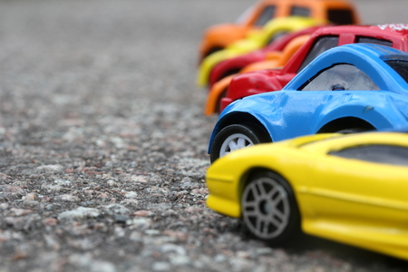 miniature colorful cars standing in line on road sale concept. Different colored cars - blue, yellow, orange, white and red color cars standing next  - car agent sale concept Standard-Bild