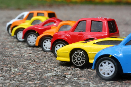 miniature colorful cars standing in line on road sale concept. Different colored cars - blue, yellow, orange, white and red color cars standing next  - car agent sale concept photo