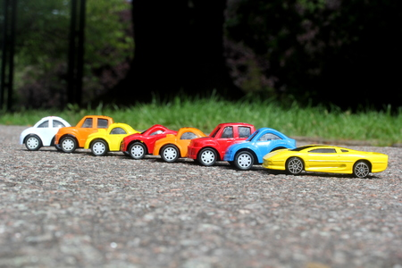 minature colorful cars standing in line on road sale concept. Different colored cars - blue, yellow, orange, white and red color cars standing side by side on road next to grass
