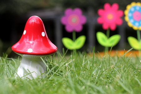 big red mushroom toy with colorful artificial flowers in background. home backyard garden objects on a sunny summer day with color flowers photo