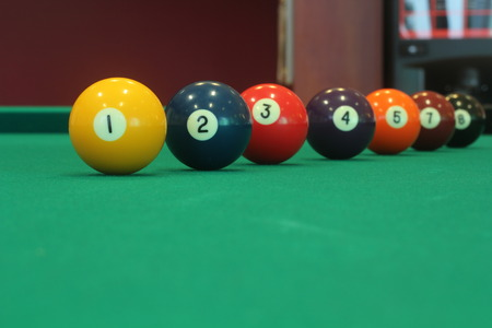 pool table: yellow snooker ball with number one on it with other colorful balls placed in a row on a table - snooker game concept image Stock Photo