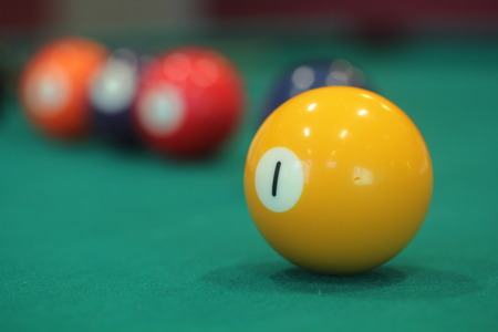 billiard balls: yellow snooker ball with number one on it with other colorful balls placed in a row on a table - snooker game concept image Stock Photo