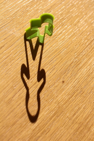 Simple single standing man shaped cutter kept on a wooden table with shadow extending from it due to sun