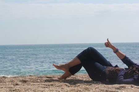 legs of happy young white lady relaxing and enjoying sunshine at the beach with thumbs up hand sign with blue sky and sea water in the background
