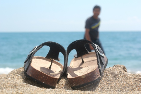 Slippers sandals kept next to sea side with a happy man walking with blue sky and sea