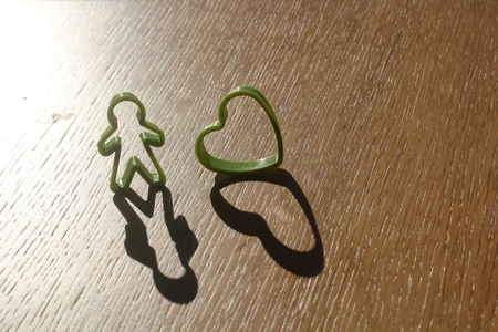 simple single standing man and heart love shaped cutter kept next to each other on a wooden table with shadow extending from it due to sun