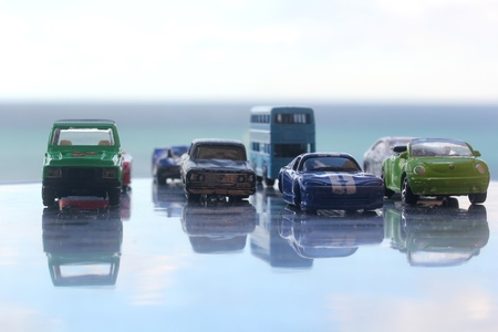Different miniature colorful (blue, red, green, black, white) cars standing in line showroom car agent sale concept