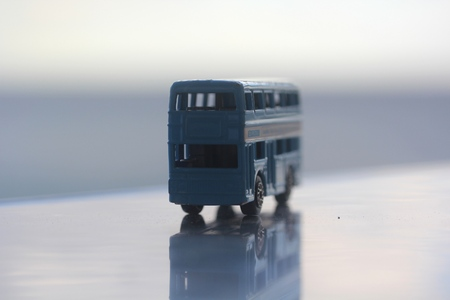 miniature colorful blue bus with reflection standing on a table with blue background